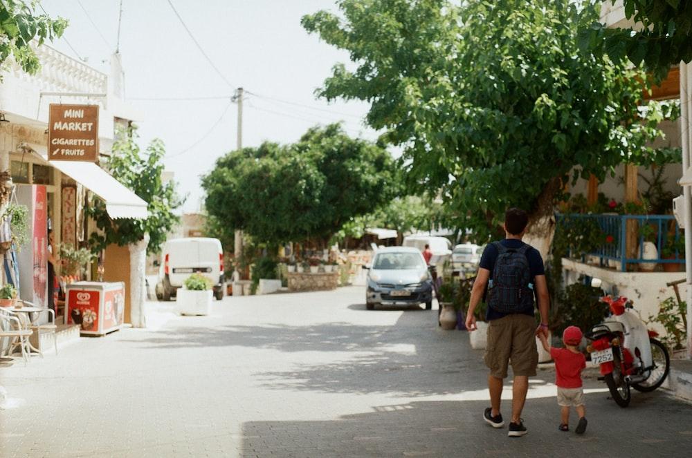 woman in red shirt walking on sidewalk during daytime