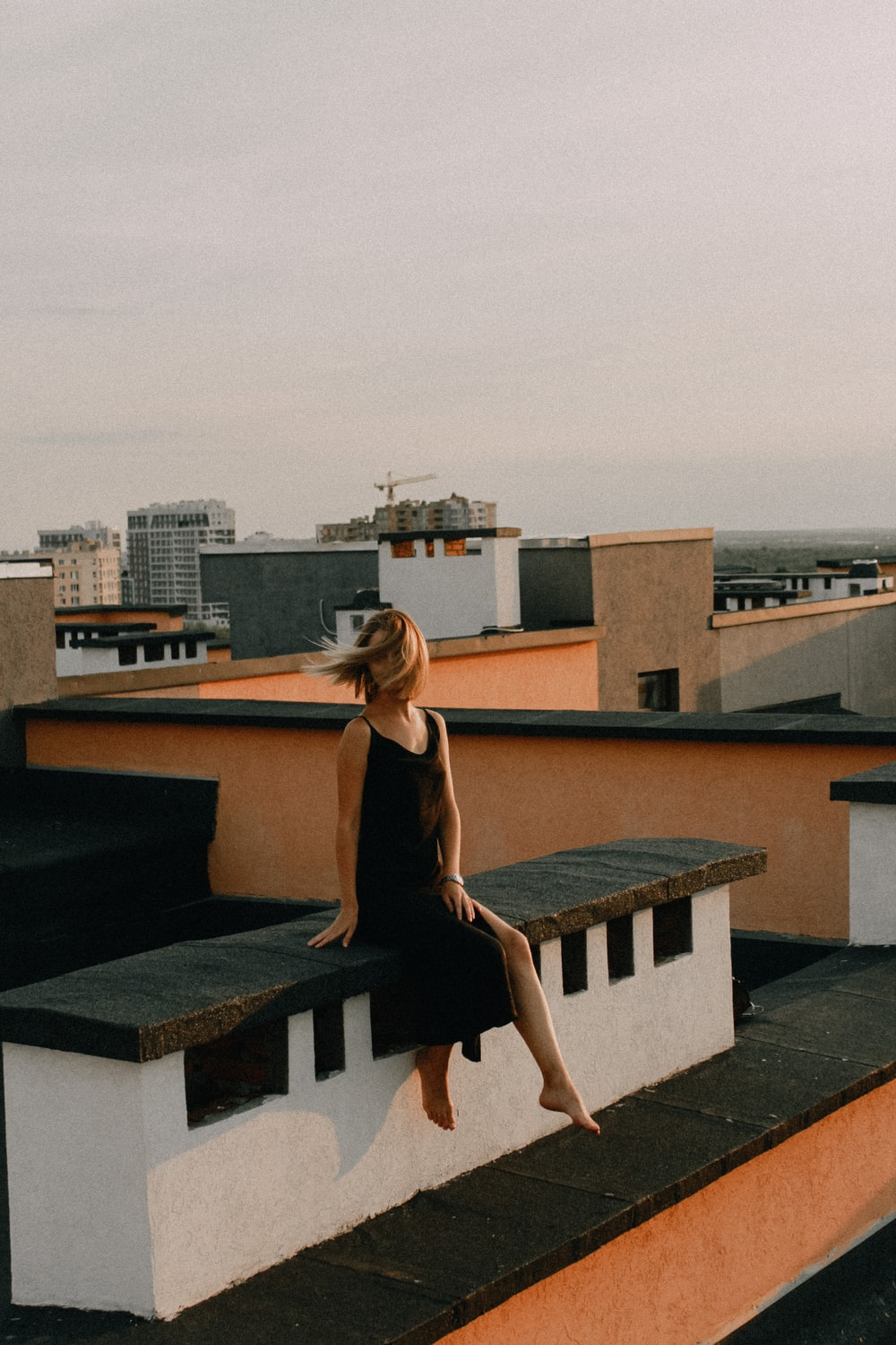 woman in black dress standing on roof top during daytime