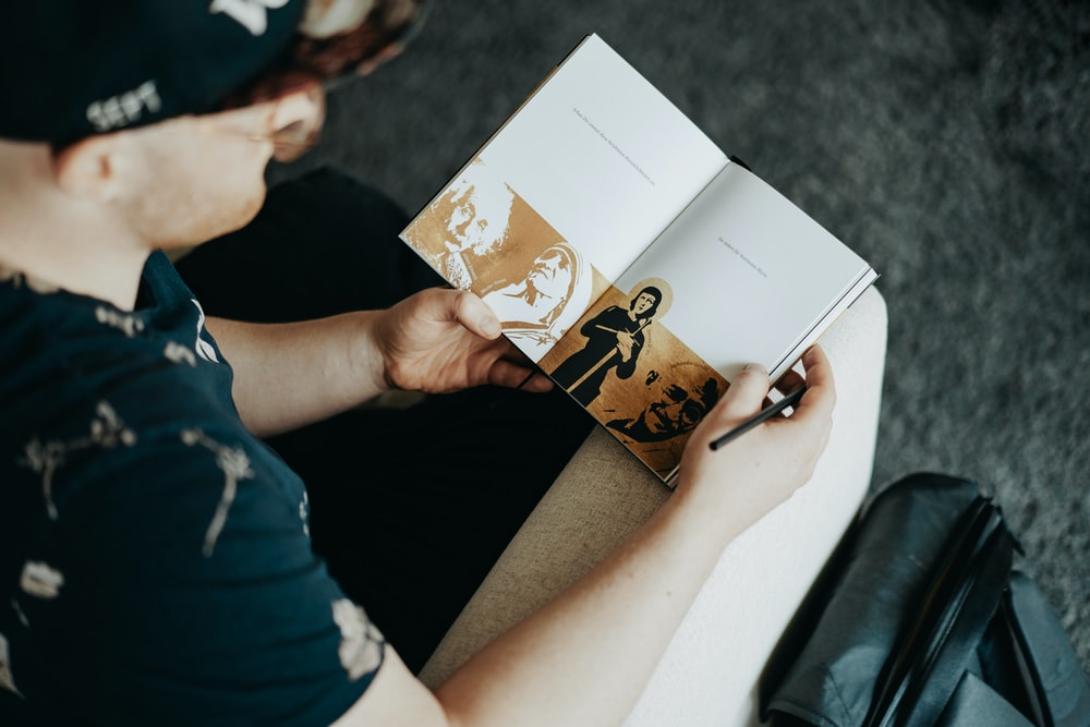 person holding white and brown book