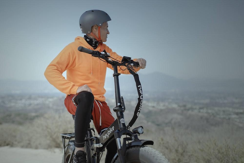 man in orange hoodie and red pants riding black mountain bike