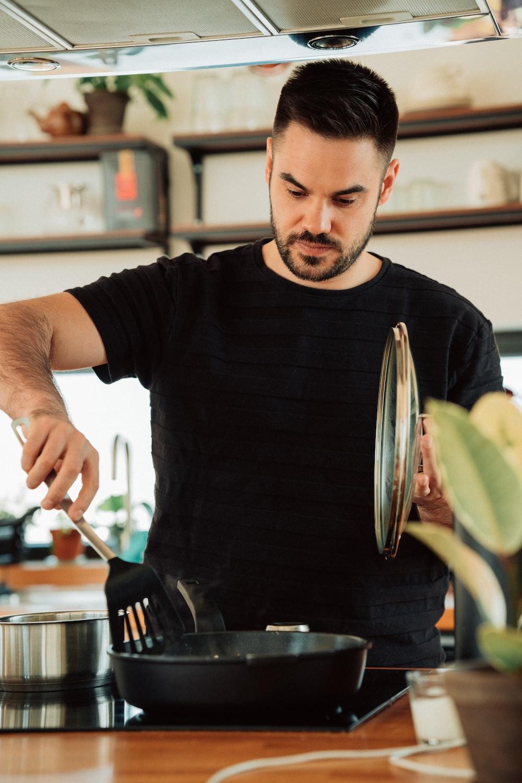 man in black crew neck t-shirt holding stainless steel fork
