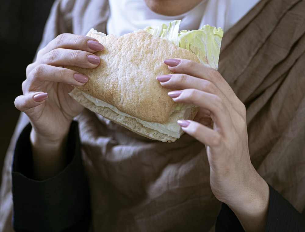 person in white shirt holding bread