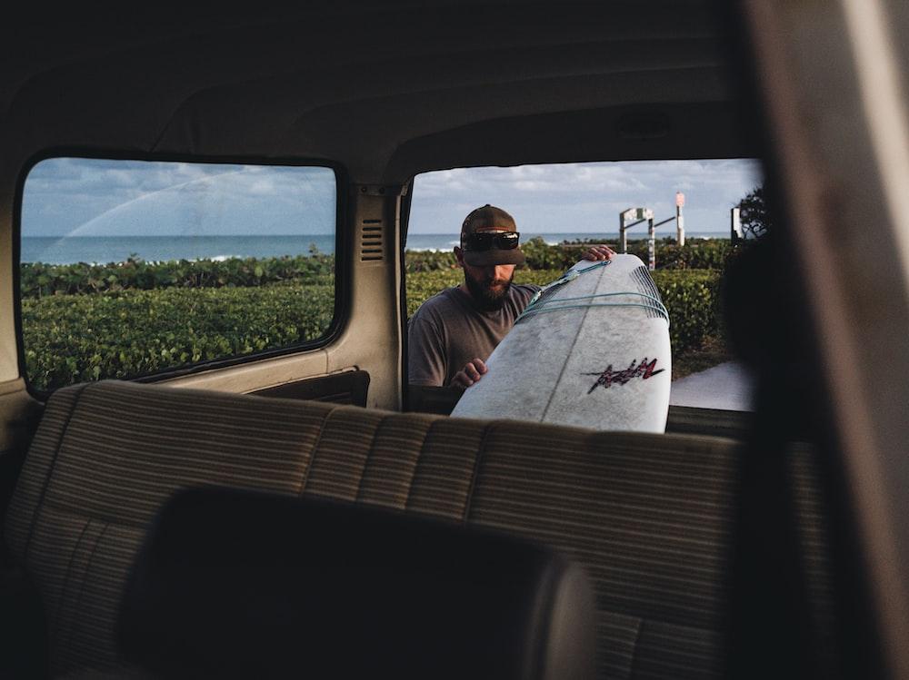 man in white shirt sitting on car seat