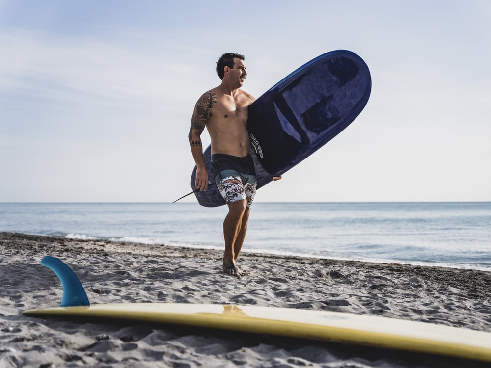 man in blue shorts holding blue surfboard on beach during daytime