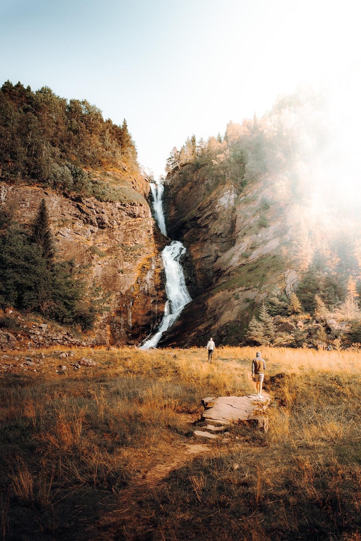 people walking on brown grass field near waterfalls during daytime