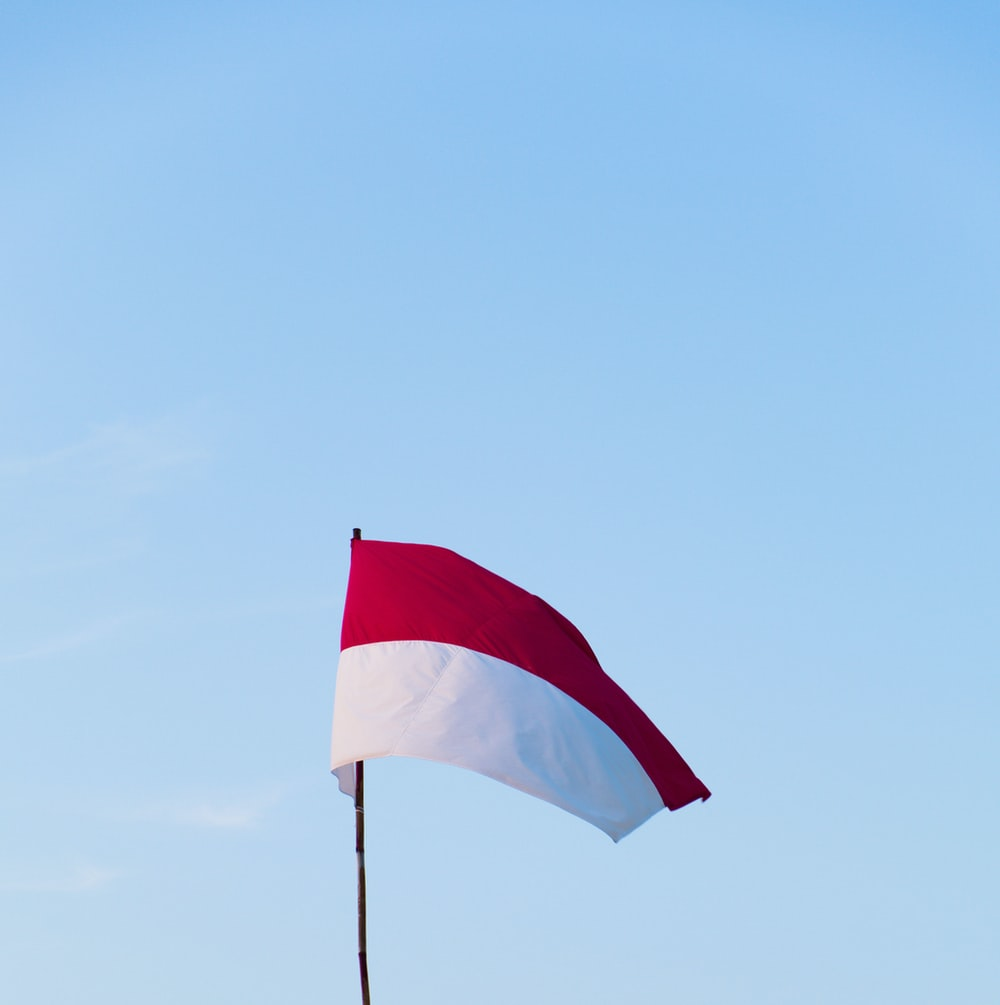 red and white flag on pole during daytime