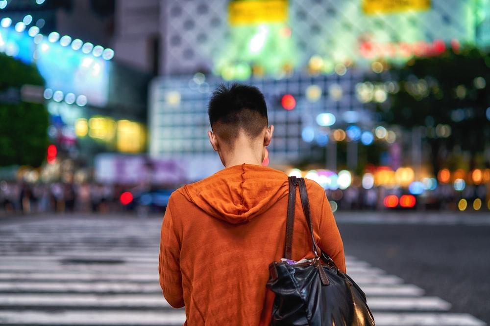 man in brown hoodie carrying black leather backpack