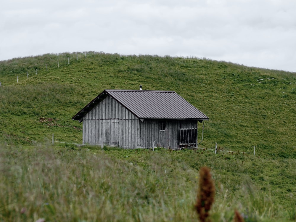 gray wooden house on green grass field during daytime