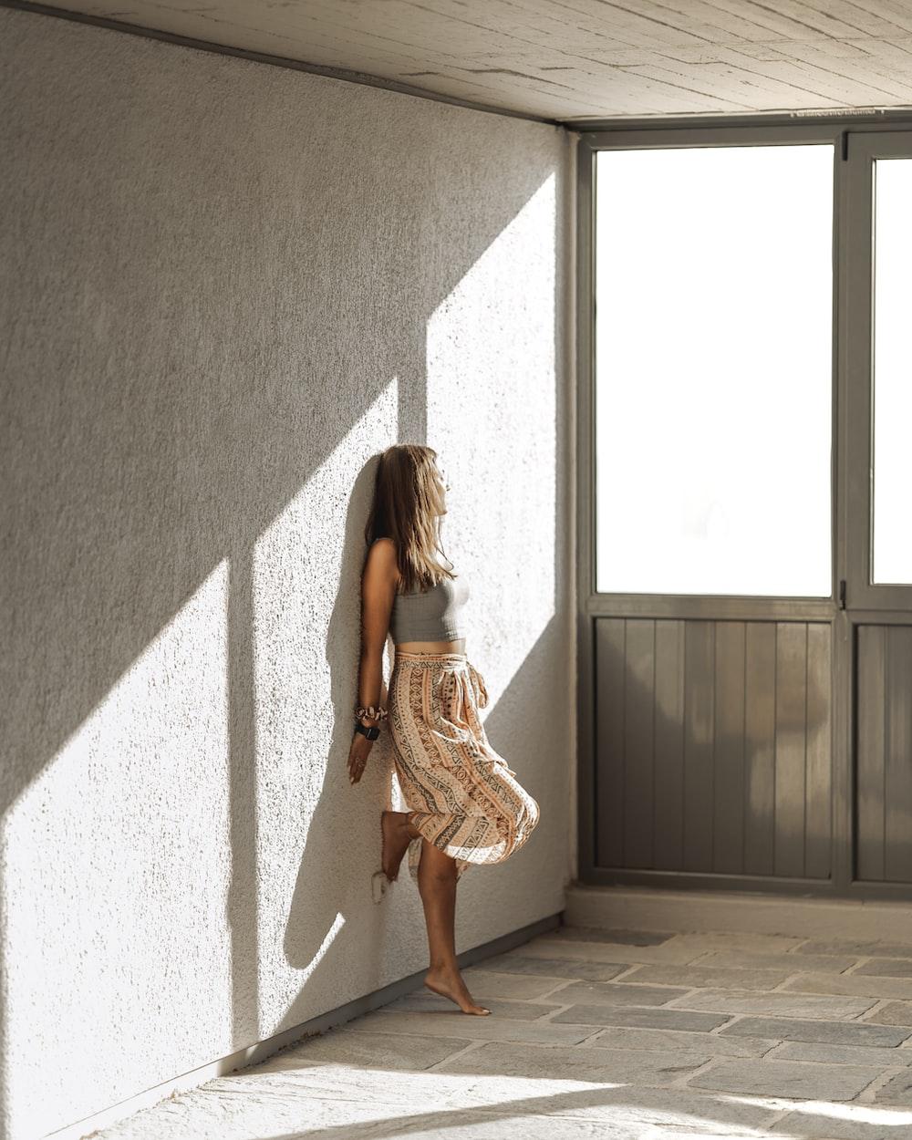 woman in brown dress standing beside gray wall