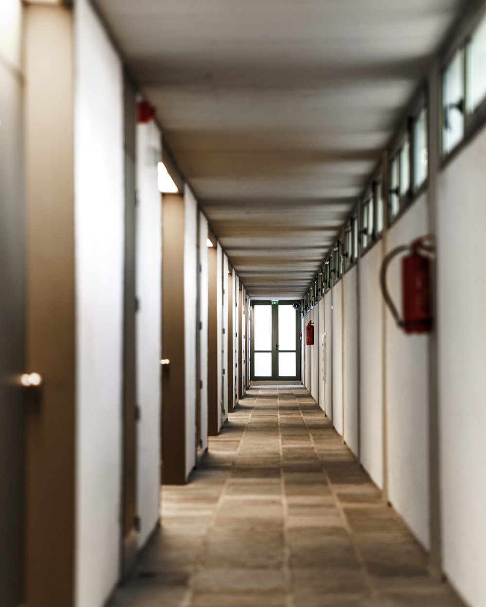 white hallway with red fire extinguisher