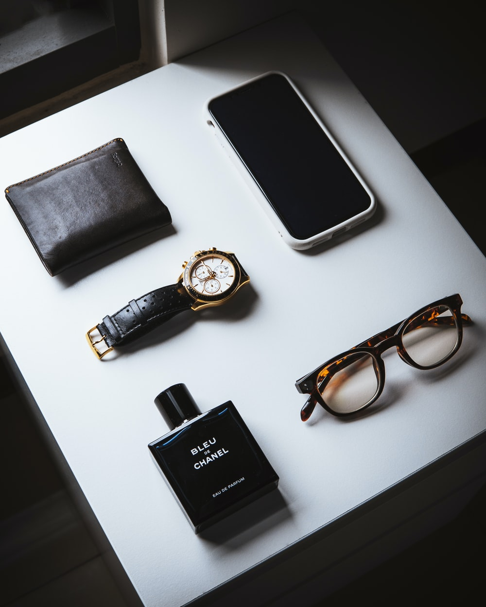 black framed eyeglasses beside black leather bifold wallet and black leather bifold wallet