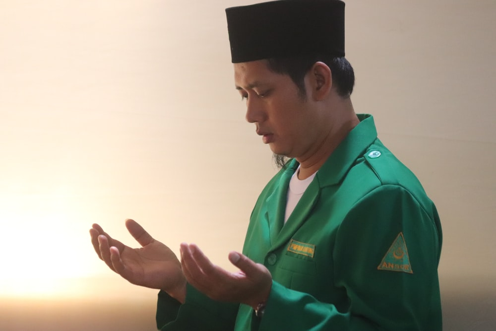 man in green uniform wearing black cap
