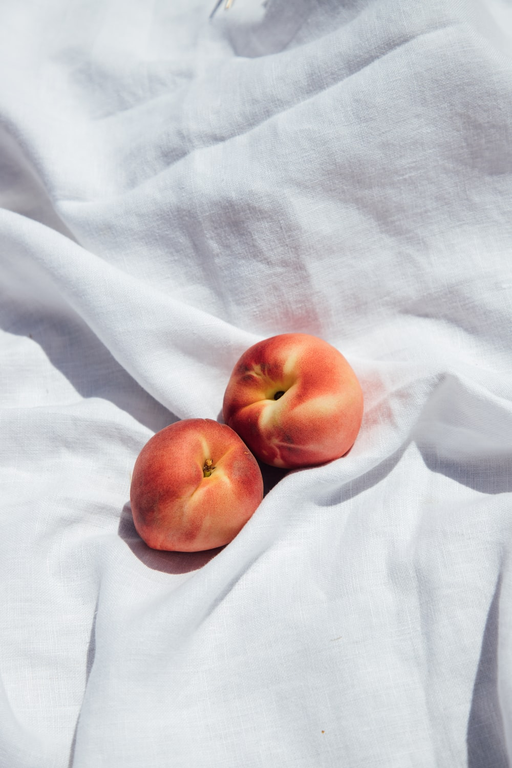 2 red apples on white textile