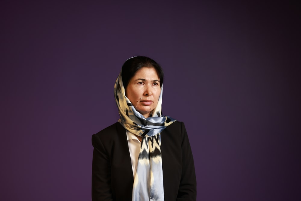 woman in black blazer and white and blue hijab
