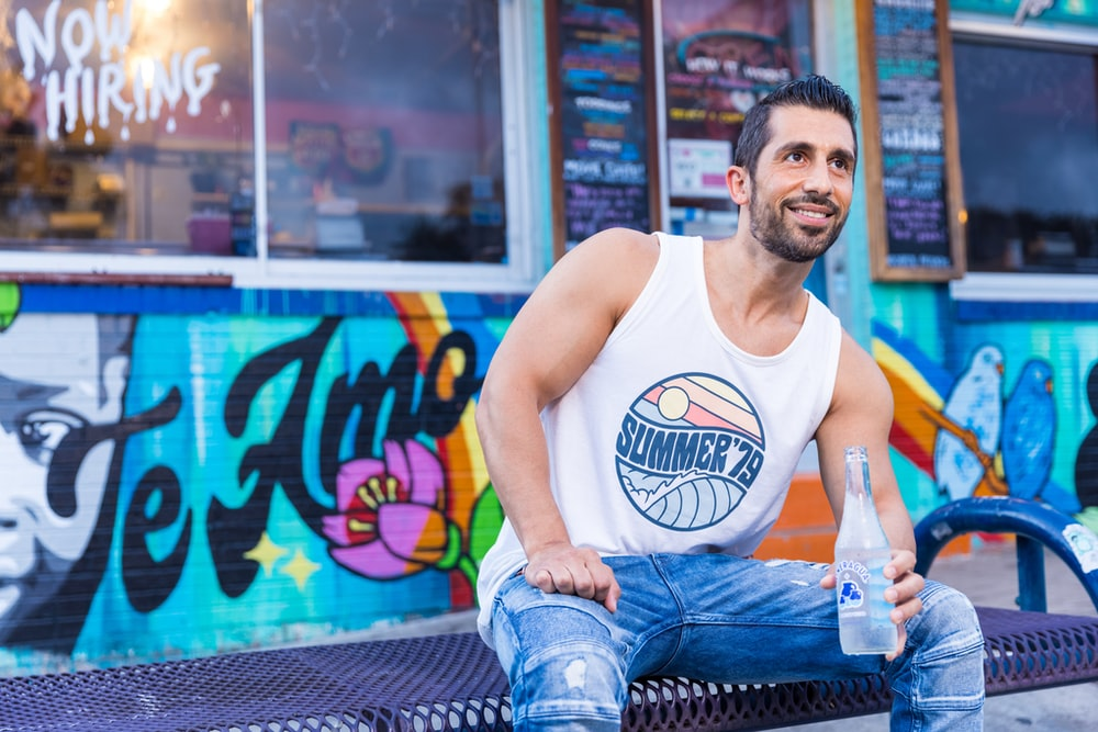 man in white tank top and blue denim jeans sitting on blue chair