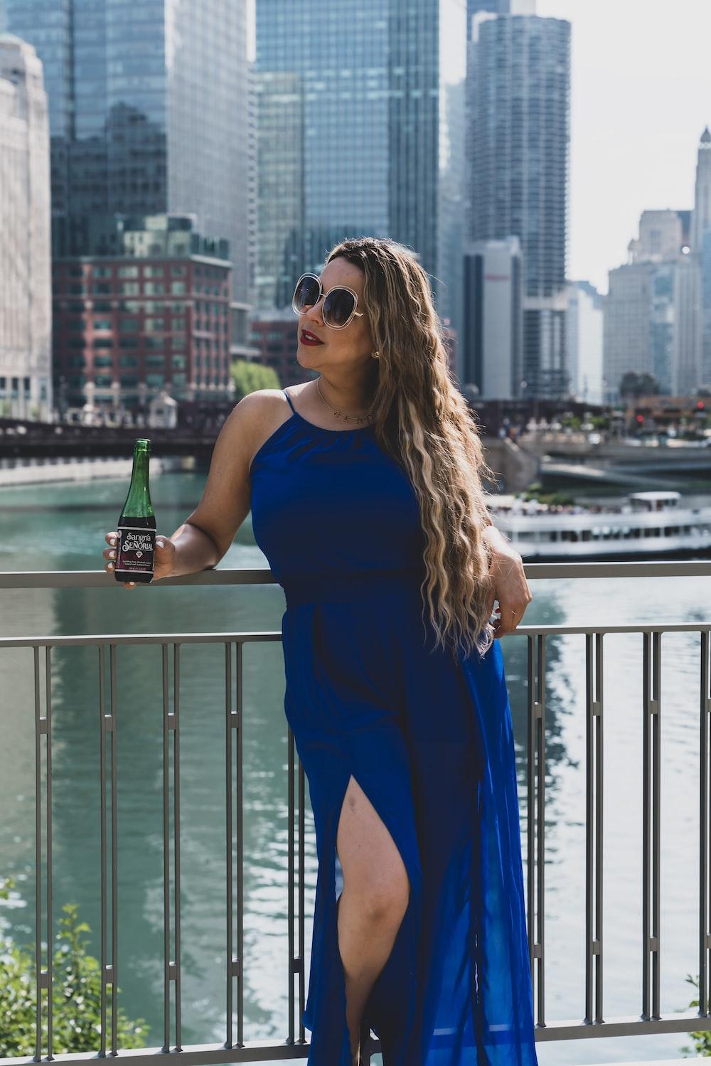 woman in blue tank top holding green glass bottle