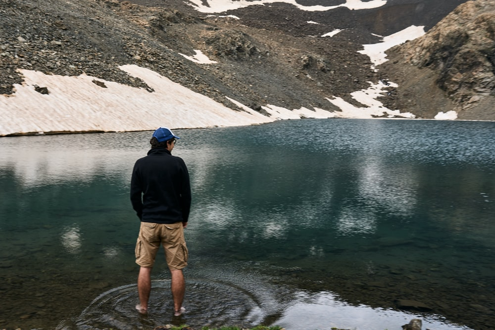 man in black jacket and brown shorts standing on lake during daytime