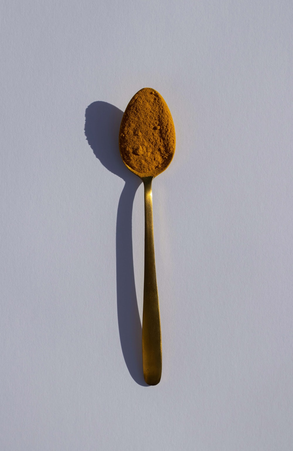 brown wooden spoon on white table