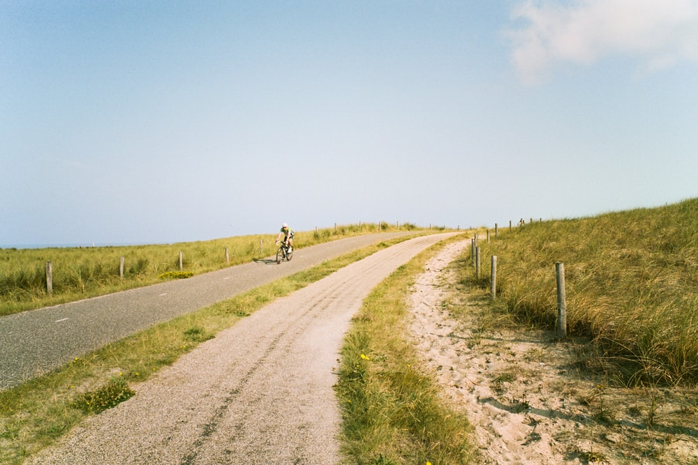 person riding bicycle on dirt road during daytime