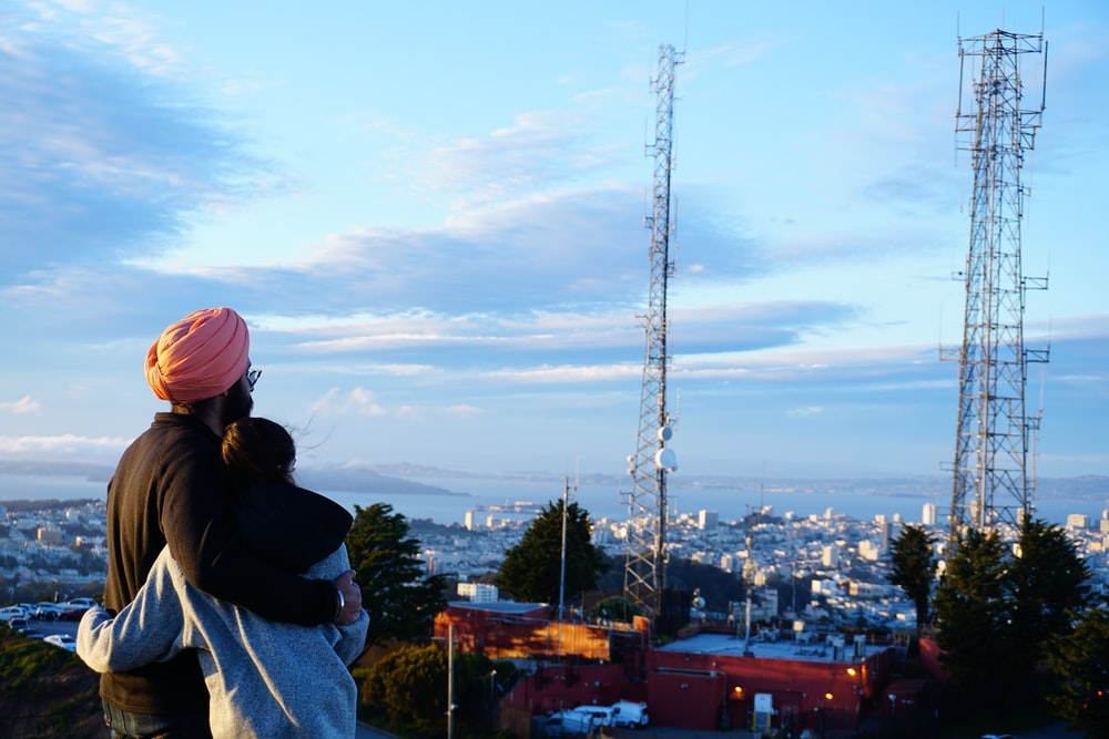 woman in black jacket and pink knit cap standing on top of building during daytime