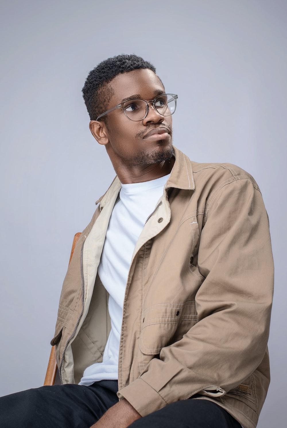man in brown button up jacket wearing black framed eyeglasses