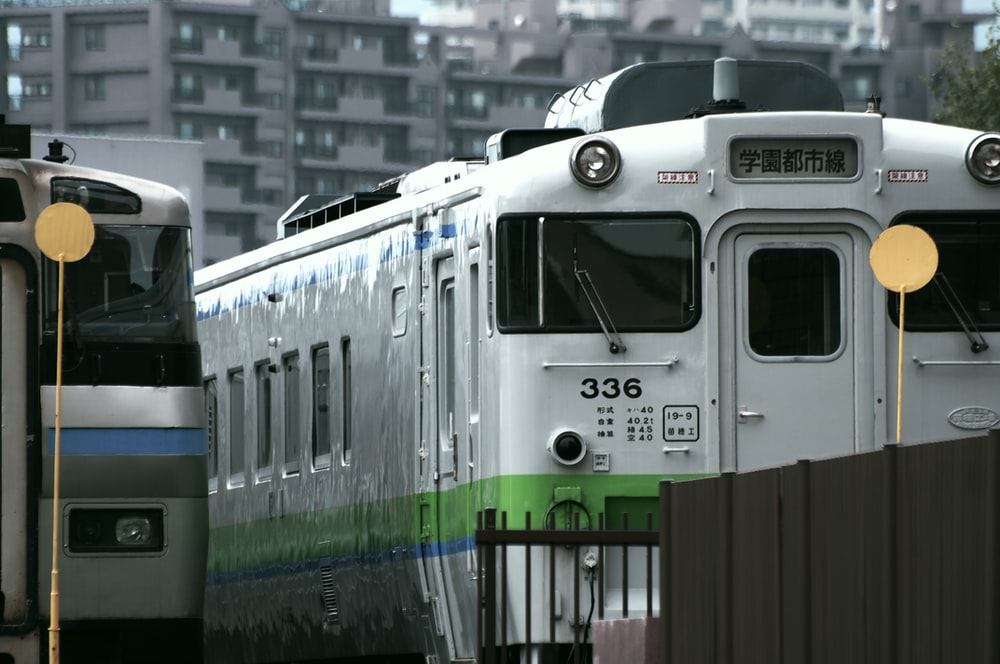white and green train on rail road during daytime