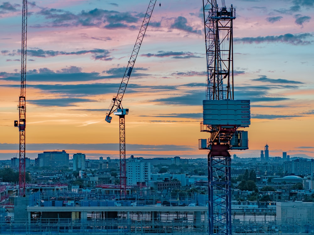 blue and white crane under cloudy sky during daytime
