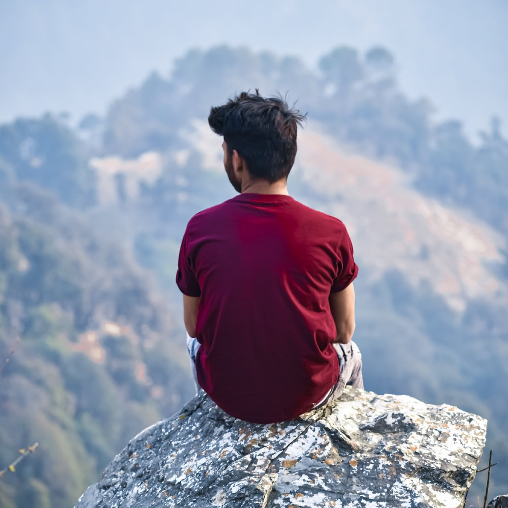 man in red crew neck t-shirt sitting on rock during daytime