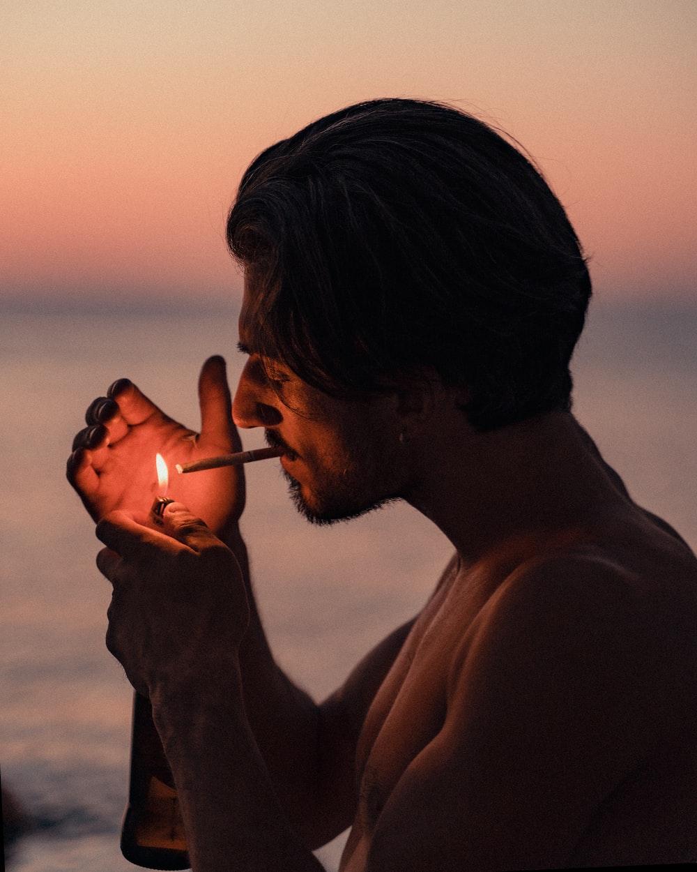 man smoking cigarette during sunset