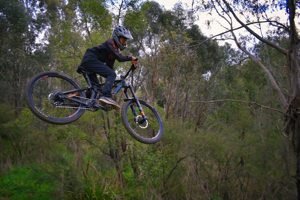 man in black jacket riding black mountain bike on forest during daytime