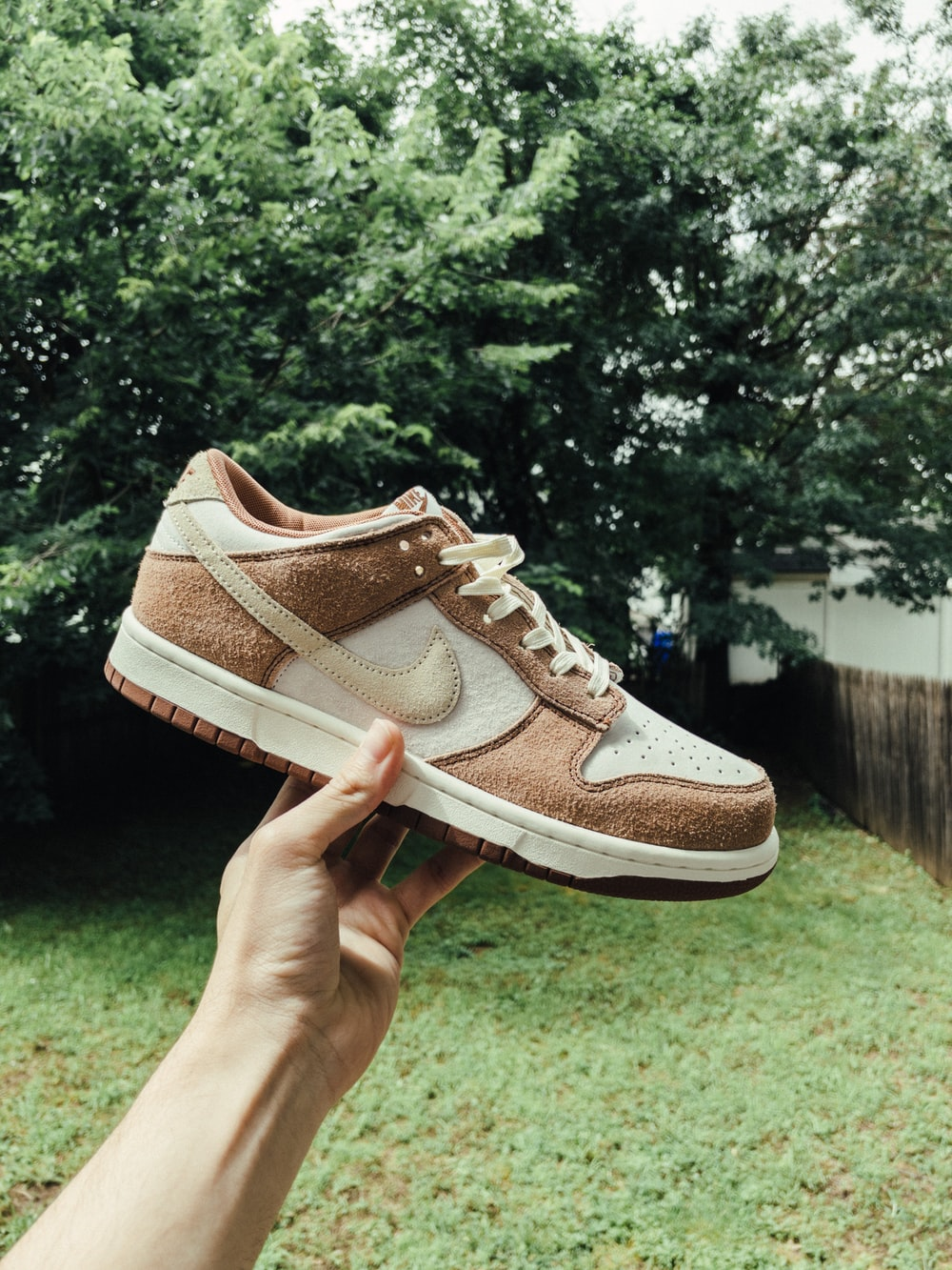person holding white and brown nike athletic shoe