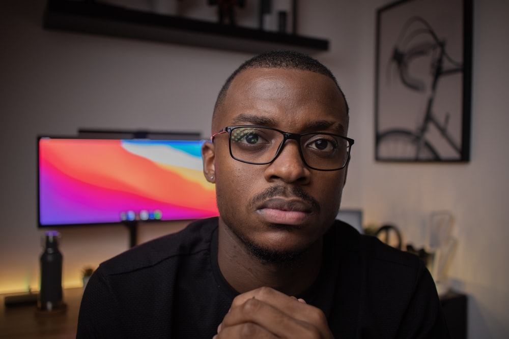 man in black framed eyeglasses and black shirt