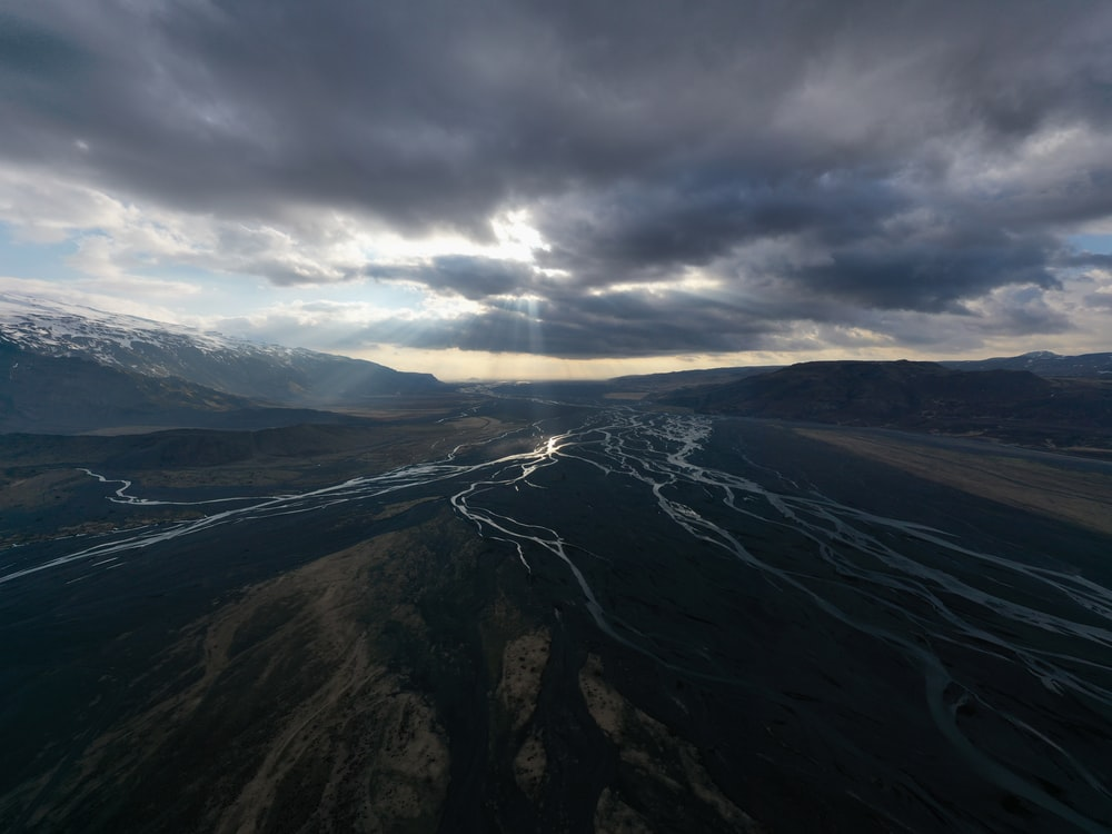 aerial view of mountains under cloudy sky during daytime