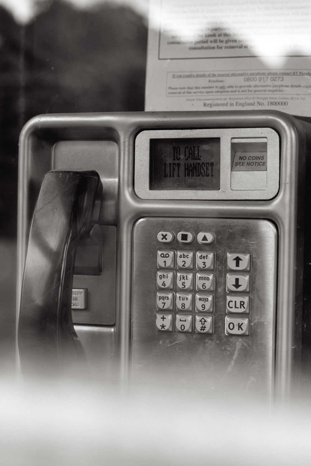 grayscale photo of telephone on table
