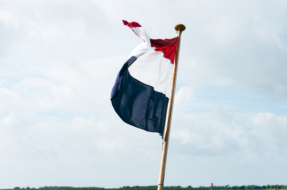 flag of us a on pole under white clouds