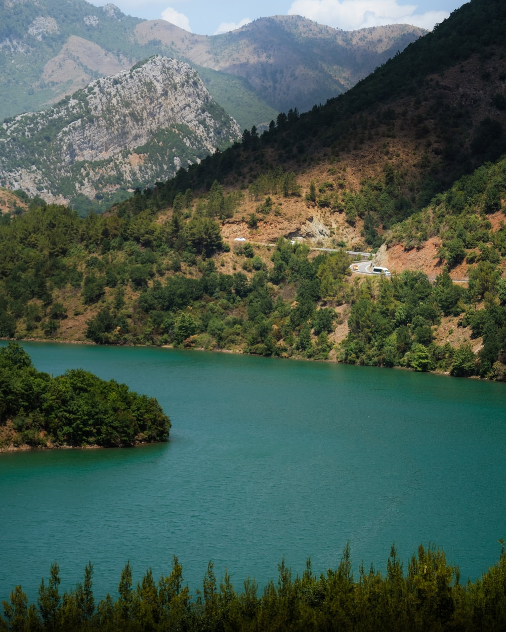 green lake surrounded by green trees and mountains during daytime