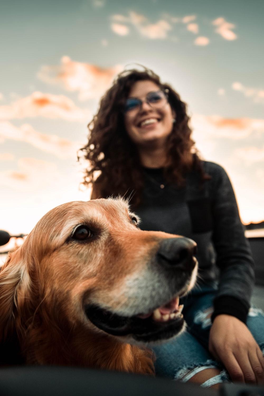 woman in black long sleeve shirt beside brown dog