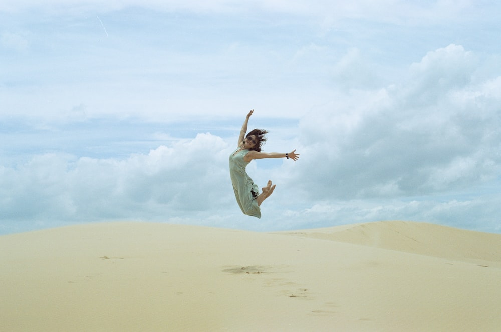 woman in white dress jumping on brown sand during daytime