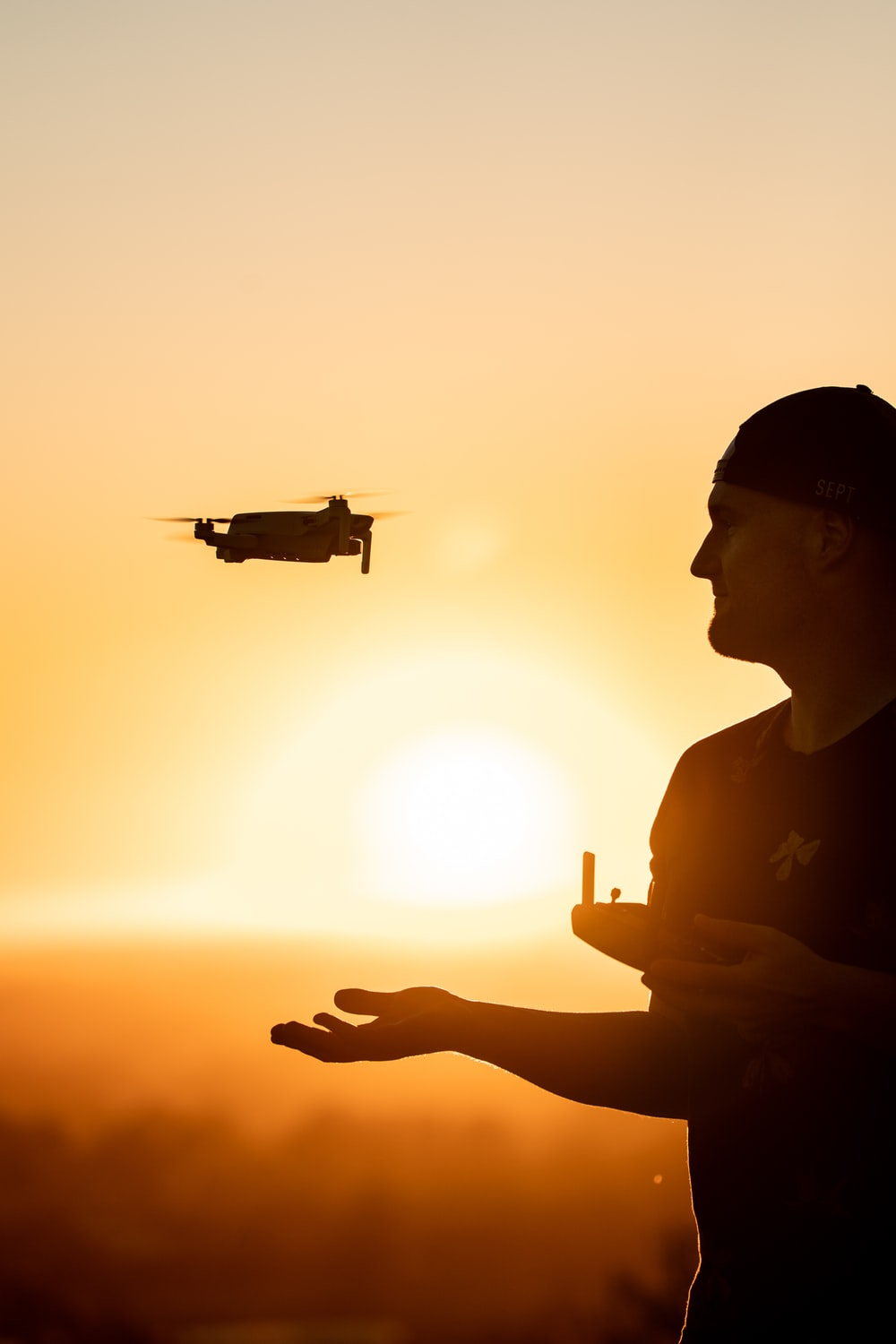 silhouette of man holding drone