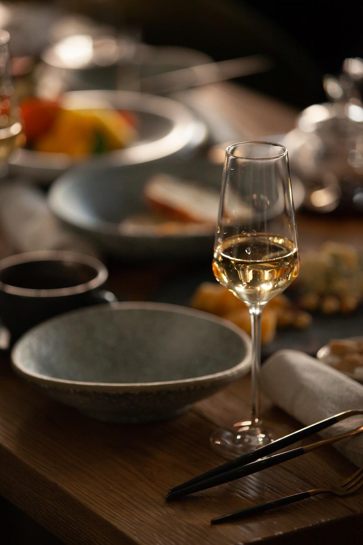 clear wine glass beside gray ceramic bowl