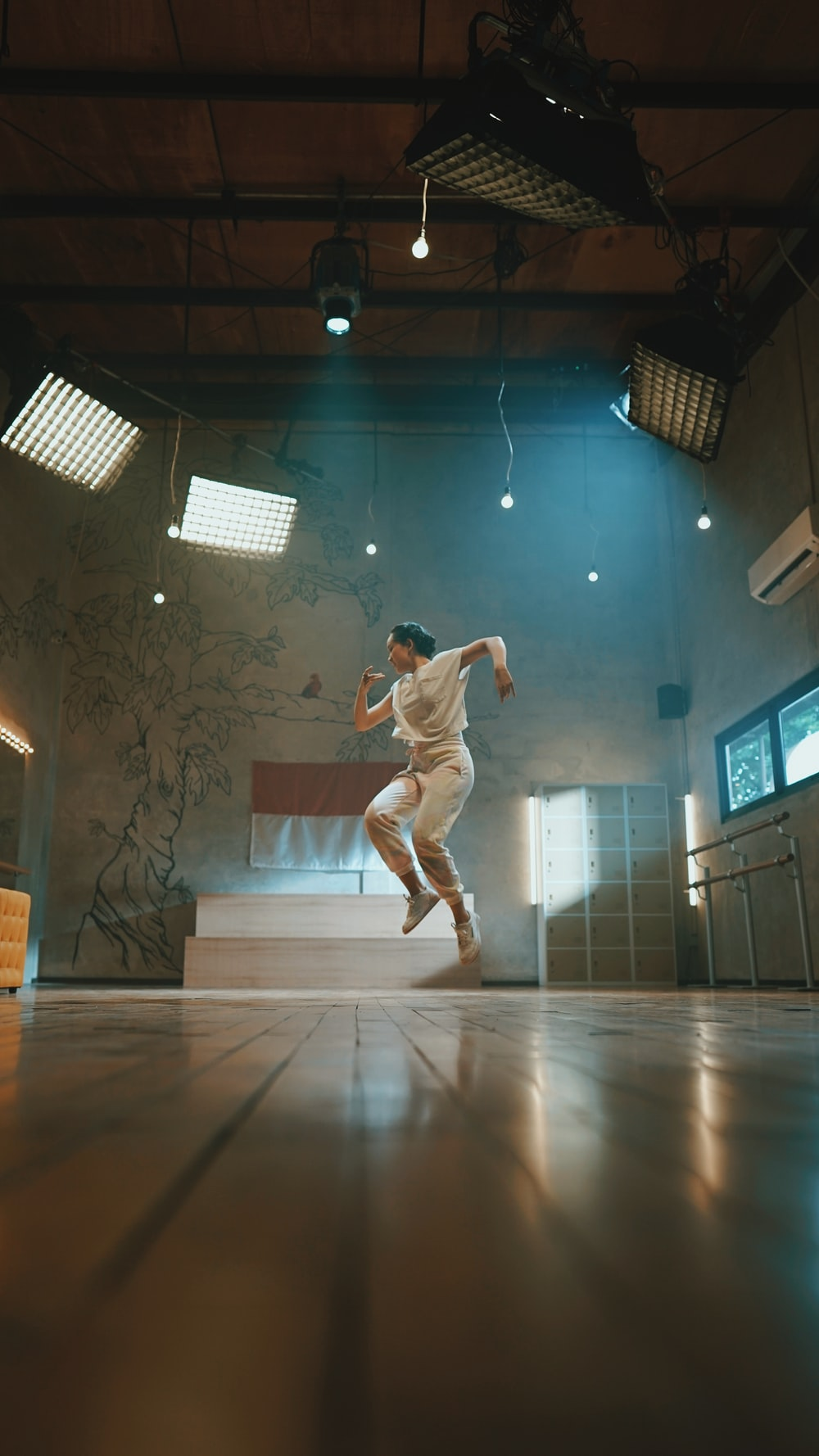 man in white shirt and pants jumping on white floor