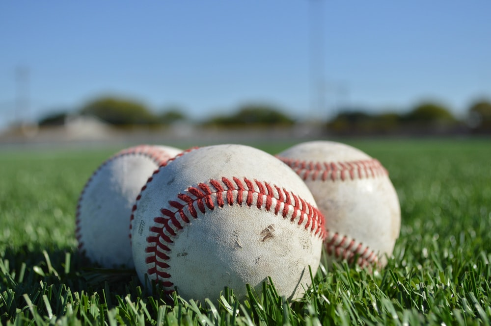 white and red baseball on green grass during daytime