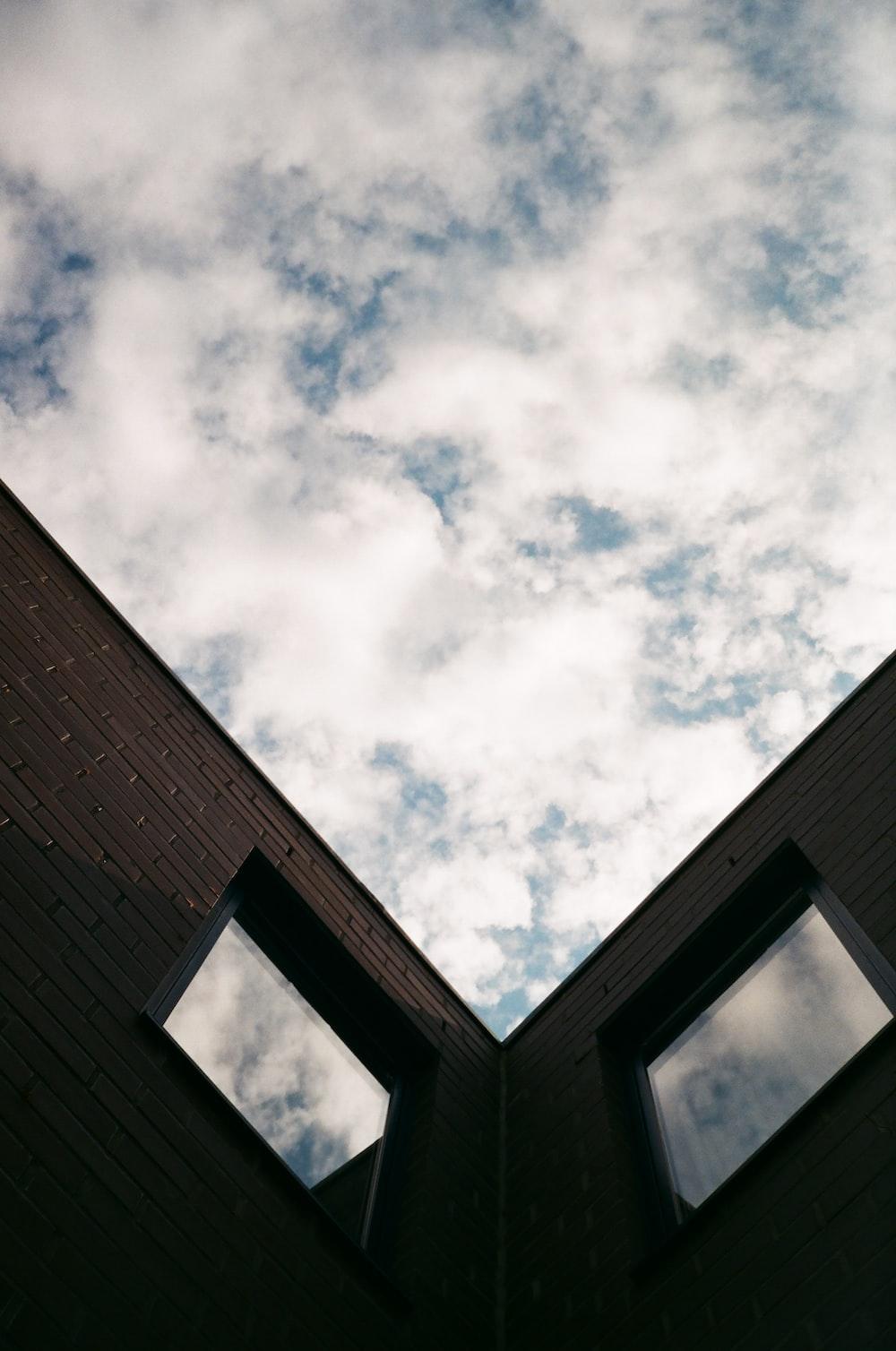 brown brick building under white clouds during daytime