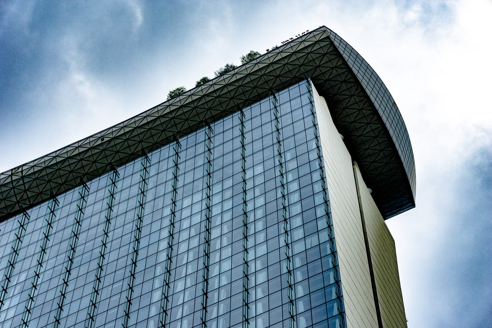 low angle photography of glass walled high rise building under blue sky during daytime