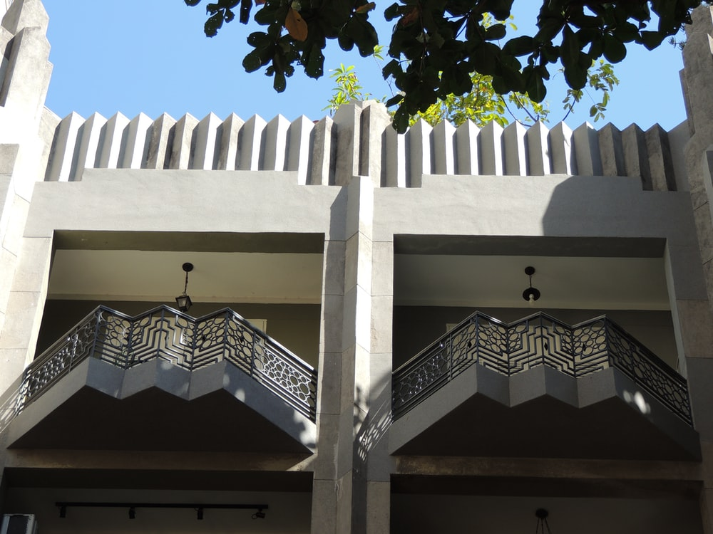 white concrete building with black metal gate
