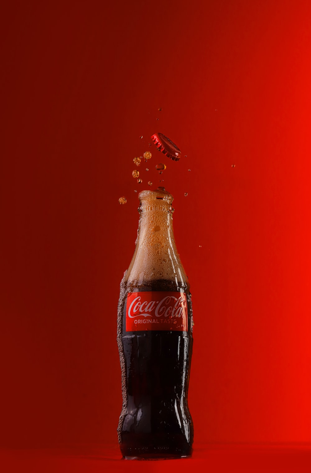 coca cola bottle on red textile