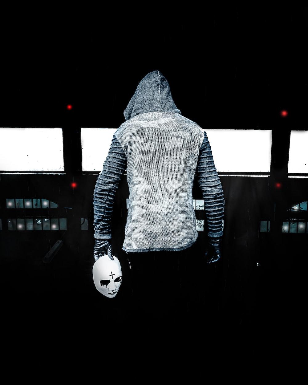 person in gray hoodie standing on black floor