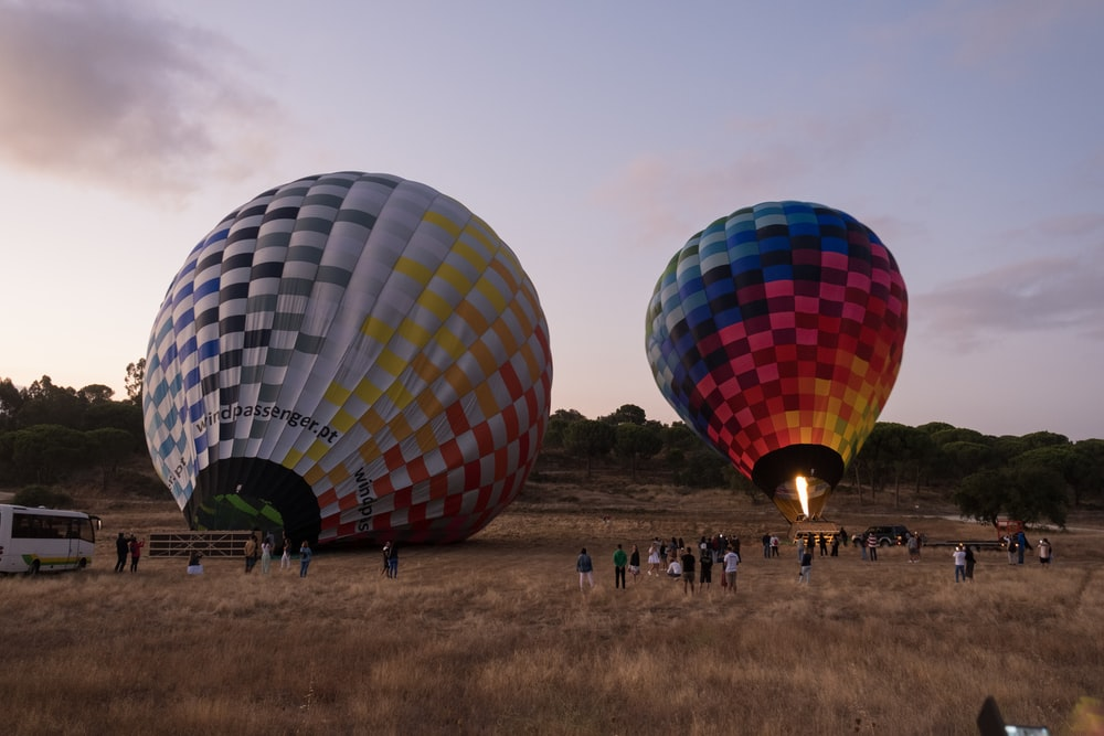 people standing near red blue and yellow hot air balloon during daytime