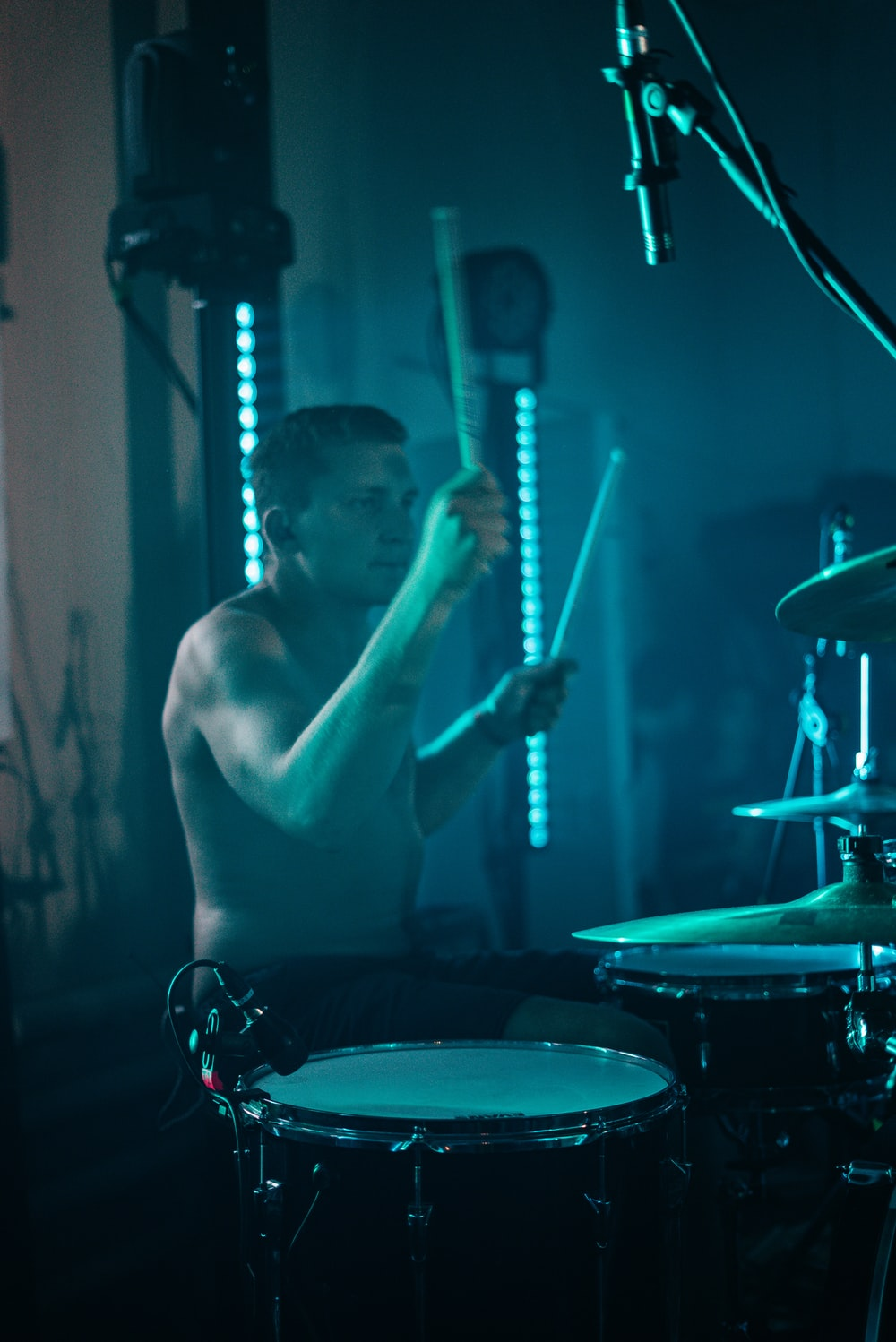 topless man playing drum and drum set