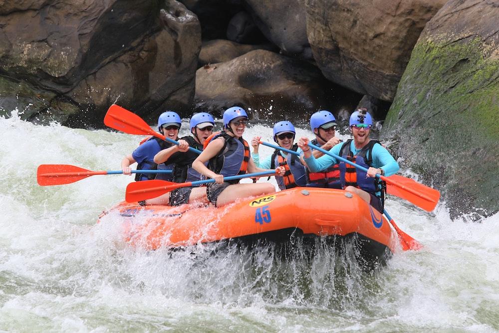 people riding orange kayak on river during daytime